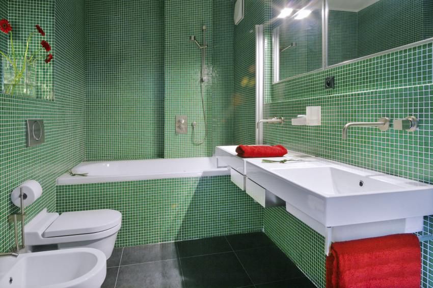 Drobné měřítko mozaiky na stěnách koupelny kontrastuje s matnou velkoformátovou dlažbou na podlaze.